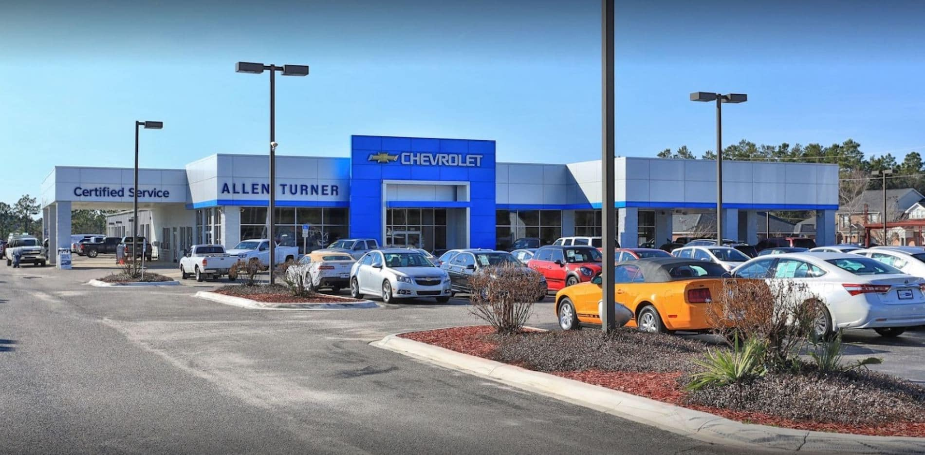 An exterior shot of a Chevrolet dealership with inventory in image
