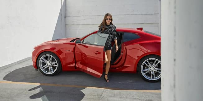 Woman getting out of Chevy Camaro