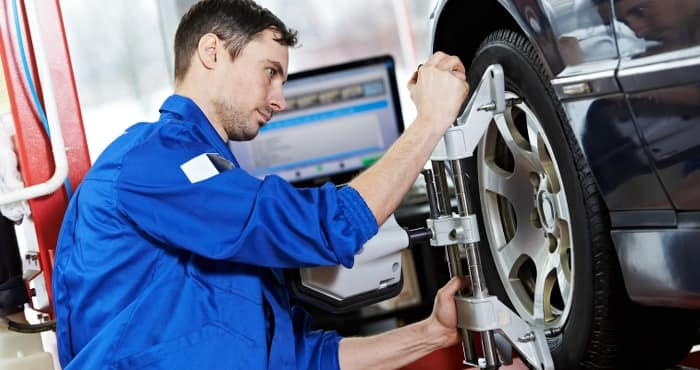 mechanic aligning tire