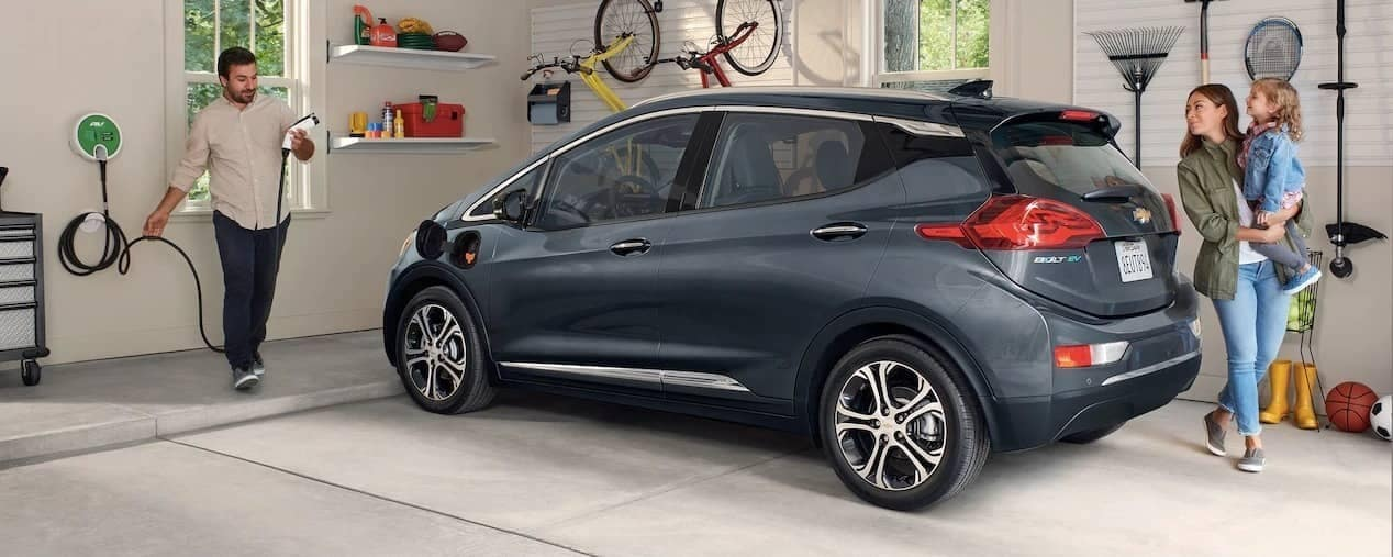 man about to charge 2019 Chevy Bolt in garage