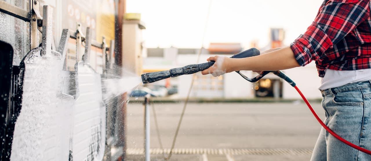 woman cleans car floor mats