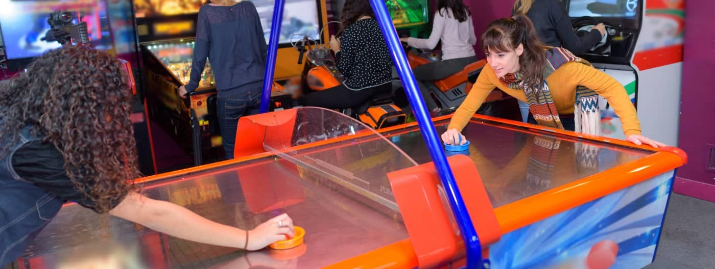 teens play air hockey at arcade