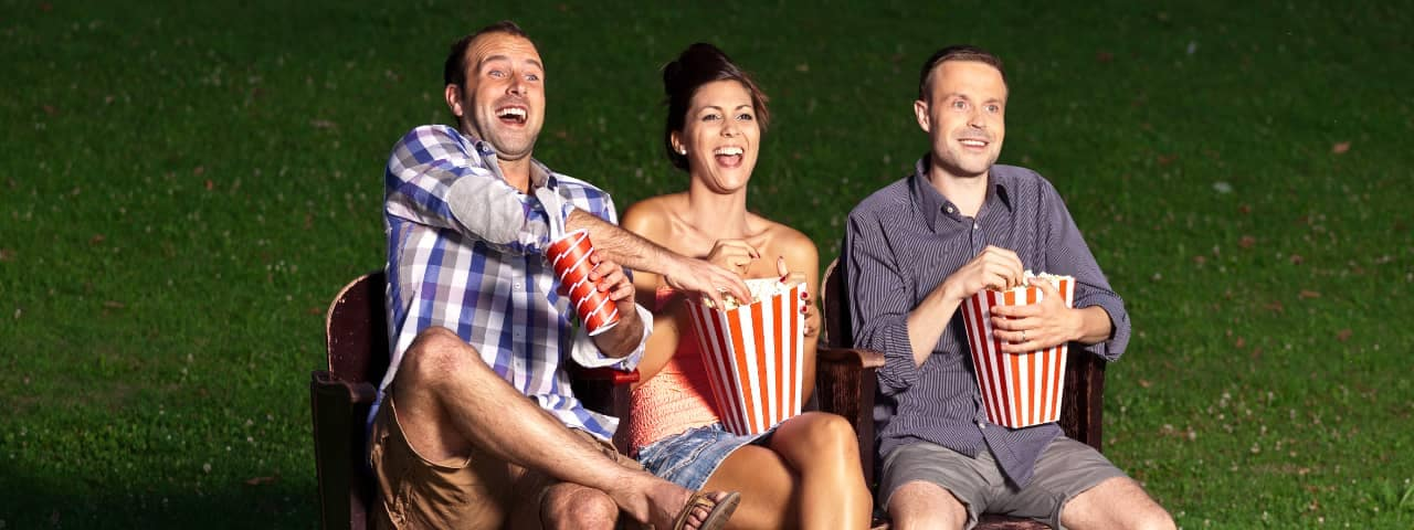 friends watch movie on park bench