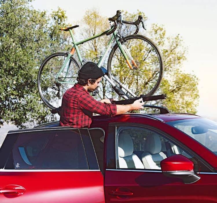 man puts bike on Mazda bike rack
