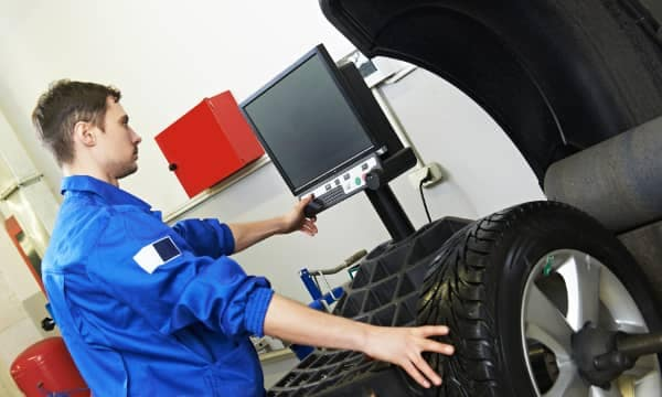 mechanic performs wheel balancing