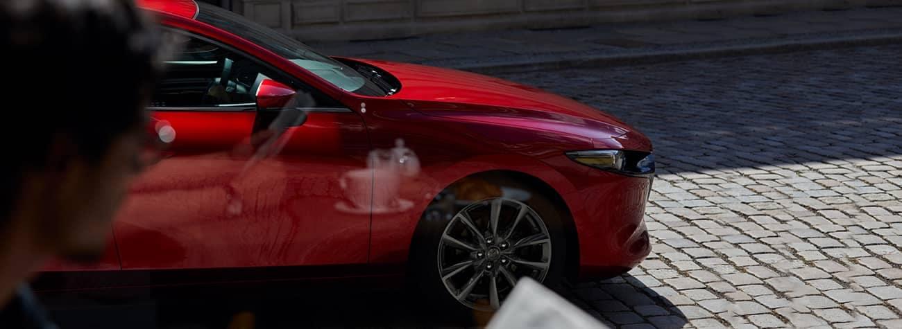 man looks at 2019 Mazda3 Hatchback through shop window