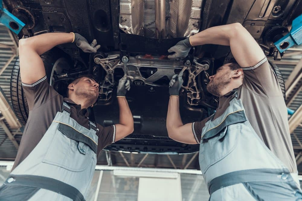 Two auto mechanics working on a vehicle