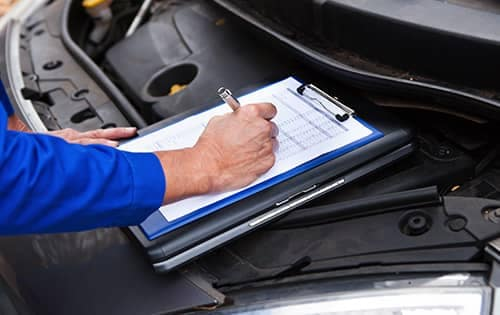 Mechanic writing on clipboard on car engine