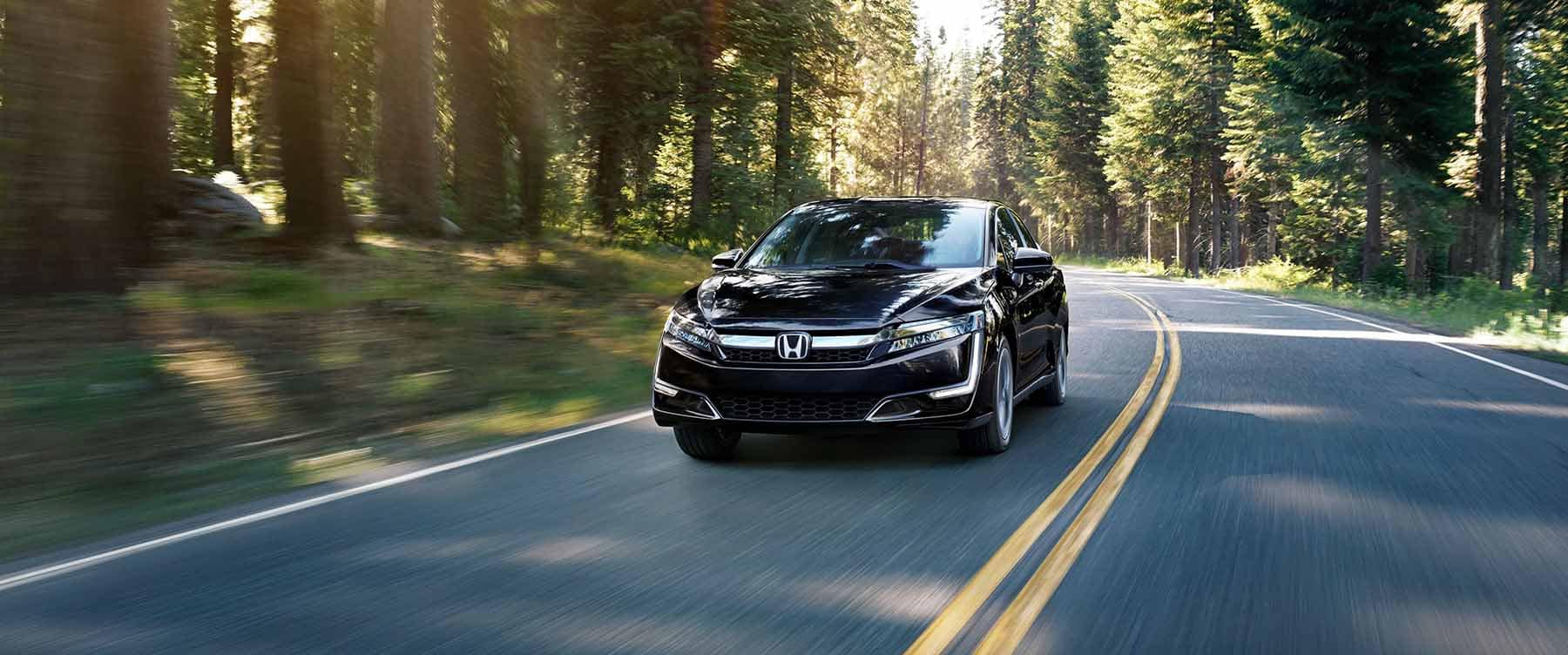 2018 Honda Clairty Plug In Hybrid Driving Down Tree Lined Street