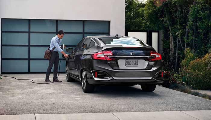 Guy unplugging his 2018 Honda Clarity Plug In Hybrid outside his home