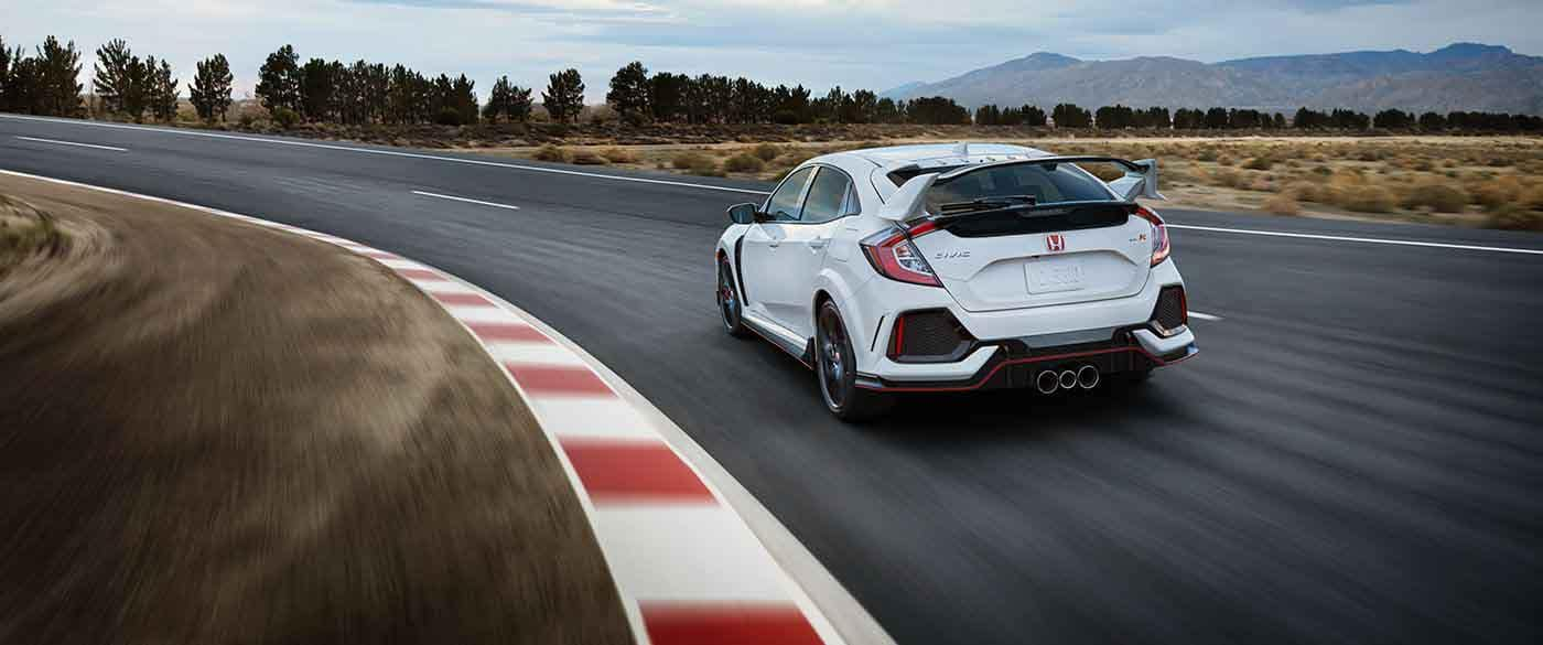 2018 Honda Civic Type R driving fast around a corner of a racetrack