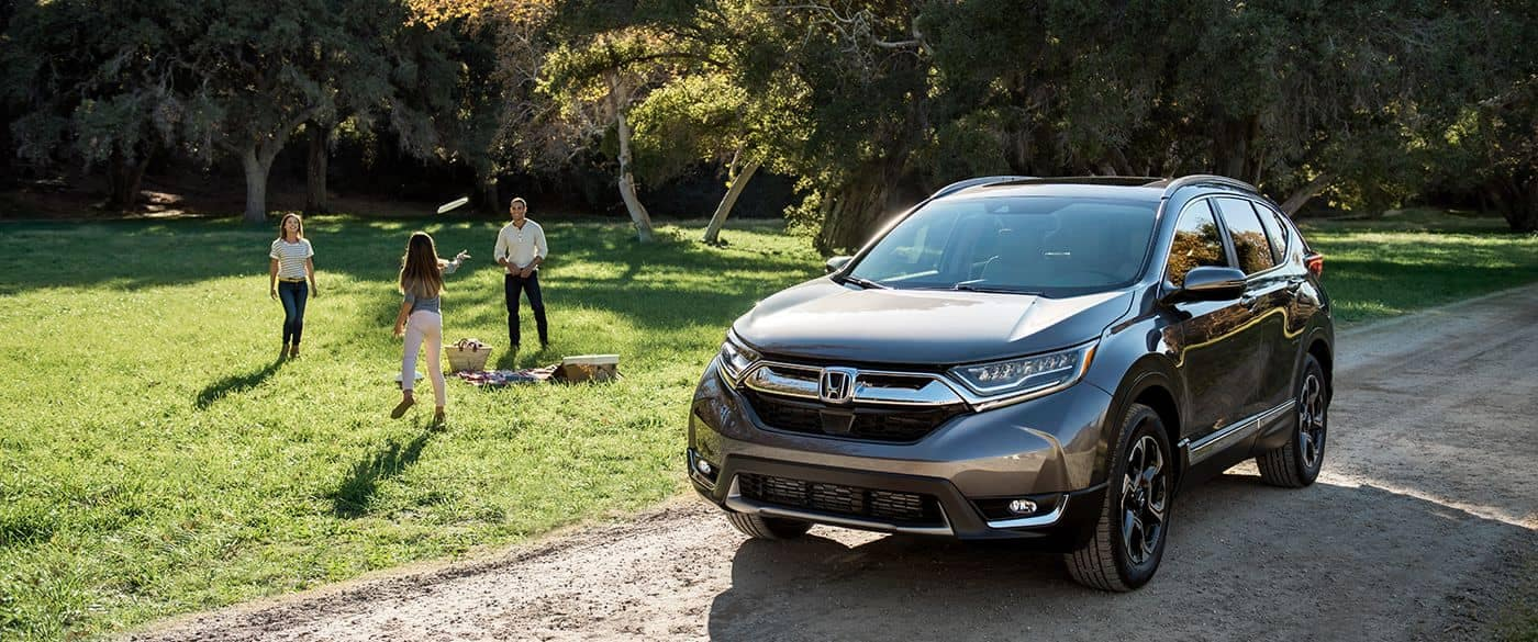 2018 Honda CR-V parked at a camp site with a family playing frisbie in the field