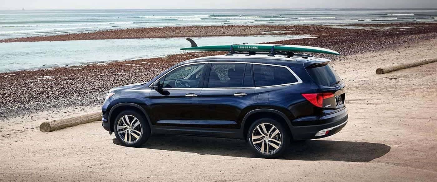 2018 Honda Pilot parked at beach with surfboard on roof rack