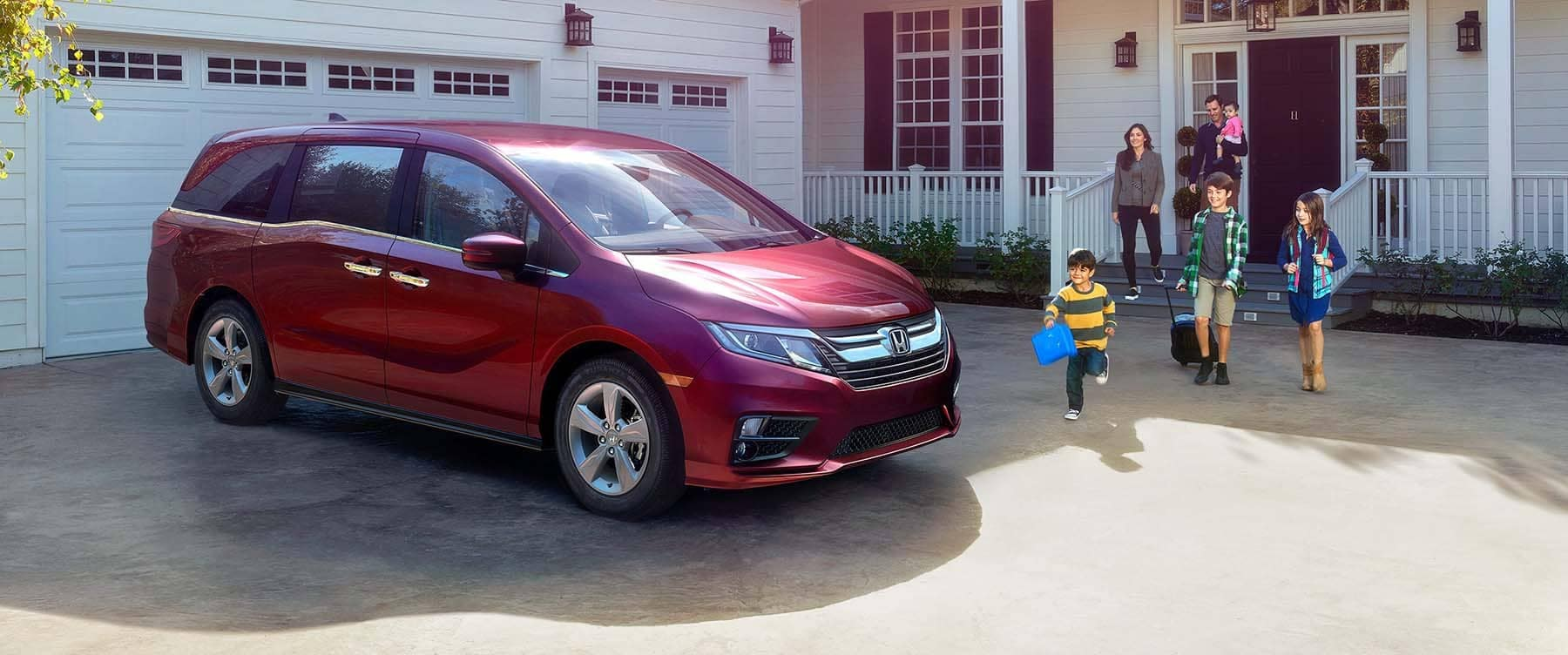 Family walking out of their home to a 2019 Honda Odyssey parked in the  driveway
