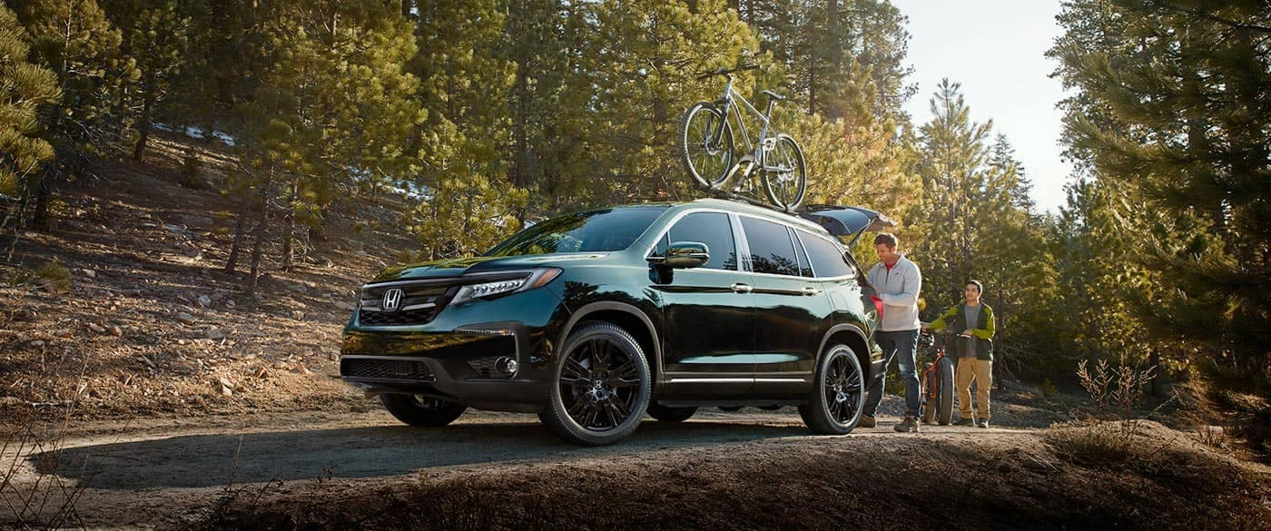 2018 Honda Pilot parked at trail with bikes on roof rack