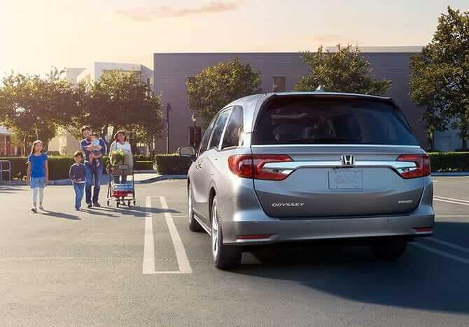 2019 Honda Odyssey next to family in parking lot