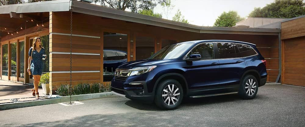 Blue 2020 Honda Pilot parked in front of modern home
