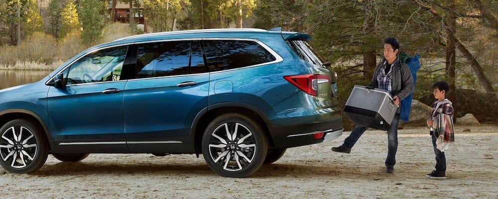 Blue 2021 Honda Pilot with dad using hands-free power tailgate to open trunk and store cargo and son next to him