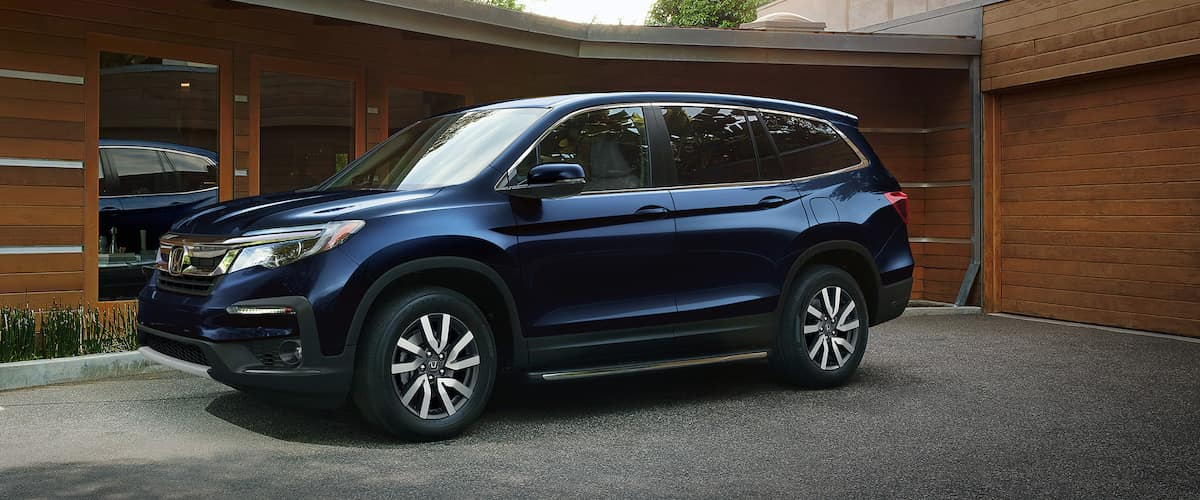 Blue 2021 Honda Pilot parked outside of brown one-story home