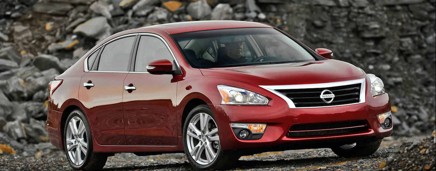 A dark red used Nissan Altima S model sitting next to a large rock pile
