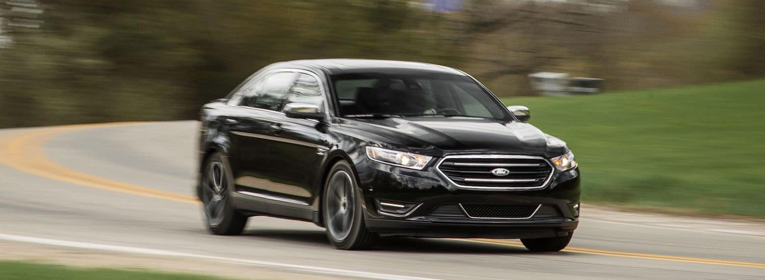 A used black 2015 Ford Taurus drives an empty road outside Atlanta