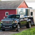 A black 2017 GMC Sierra Denali 3500HD towing a trailer in front of a barn