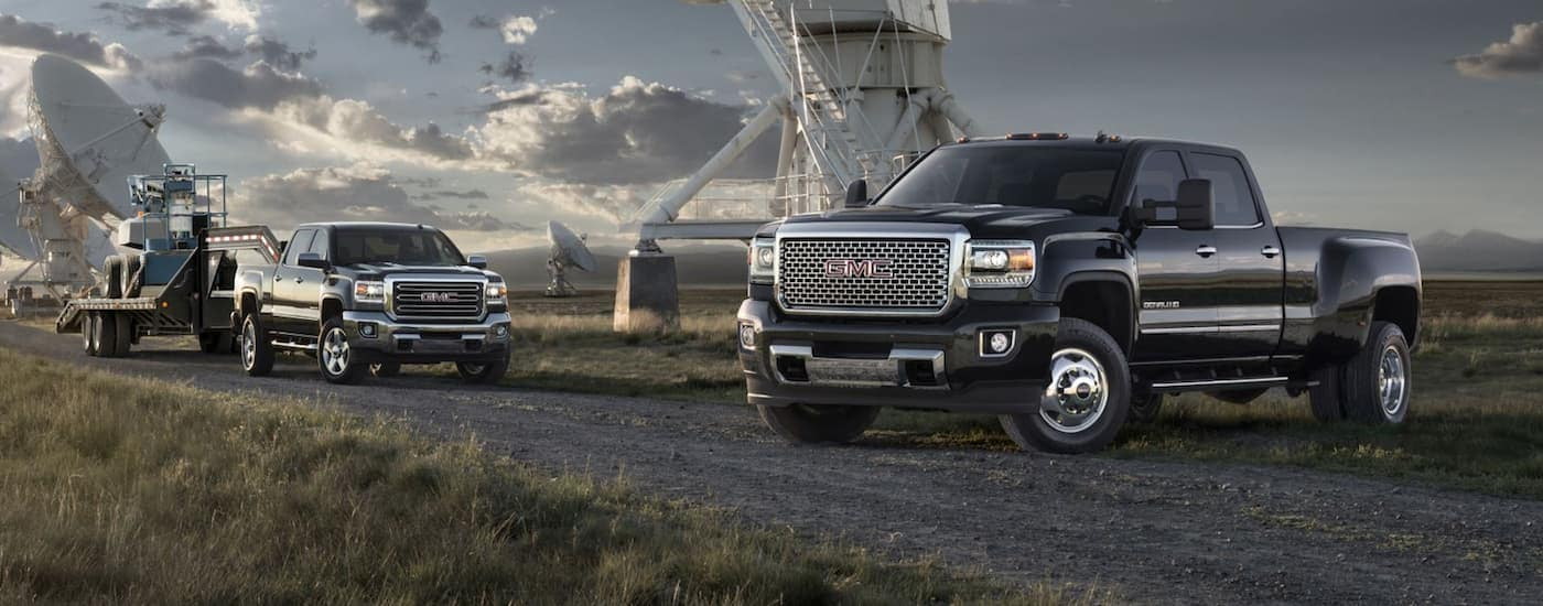2 black GMC Sierra heavy duty diesel trucks in a field with large satellite recievers