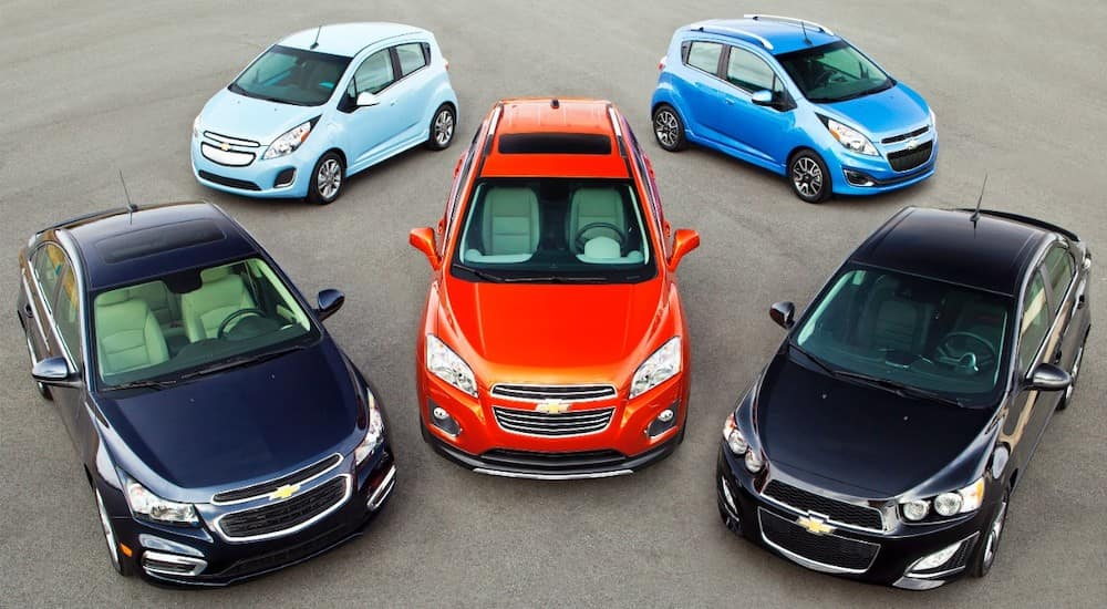Four Chevy cars, in blue and black, are parked around an orange Chevy car to display their 2014/2015 car lineup. When searching for used cars, Atlanta , GA has great options.