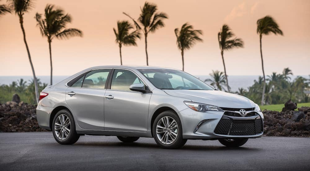 A silver 2016 Toyota Camry with palm trees in the back at sunset. Another example of popular used cars near Atlanta GA