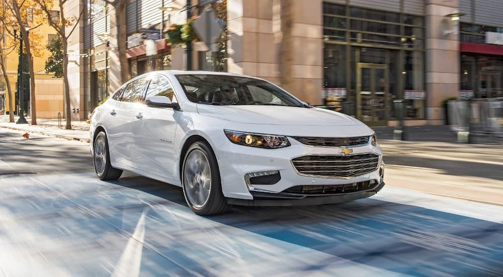 A white 2018 Chevy Malibu is driving in a city. The Malibu is a popular example of used cars near Atlanta GA being purchased.