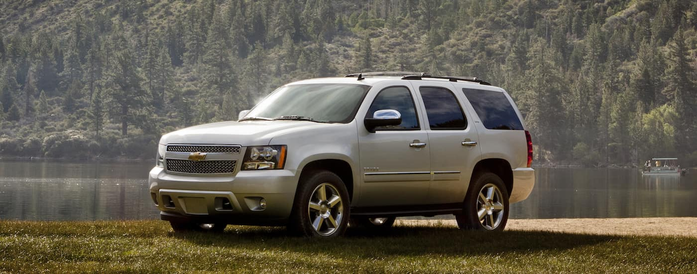 A silver 2014 Chevy Tahoe parked next to a local Hiram lake as the morning dew clears