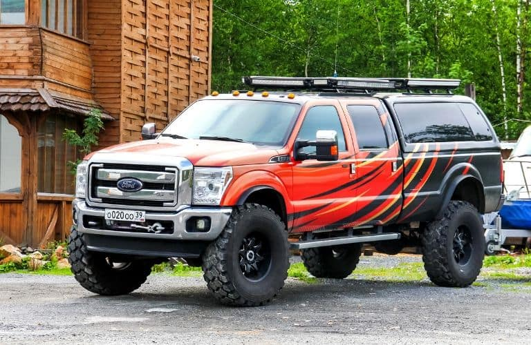 lifted Ford pickup truck with red and black exterior paint