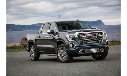 2019 GMC Sierra Denali exterior shot with gray blue paint color parked by a lakeside near water, rocks, and grass