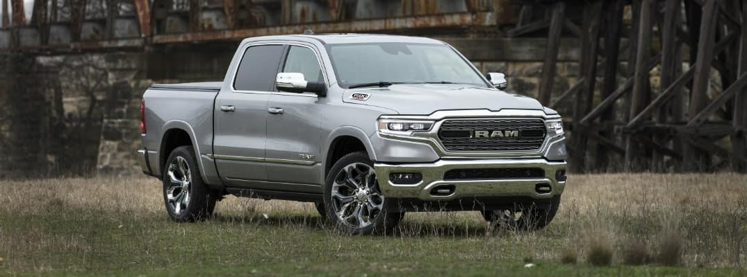 2020 Ram 1500 EcoDiesel exterior shot with gray metallic paint color parked in a grass clearing near an old and rusty bridge