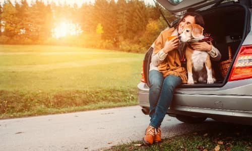 a woman sitting with her dog on the edge of her car's open trunk