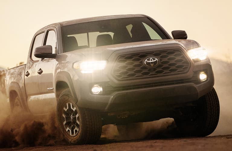 2020 Toyota Tacoma exterior front shot with LED headlights on driving through a desert as dust is kicked up by tires into clouds