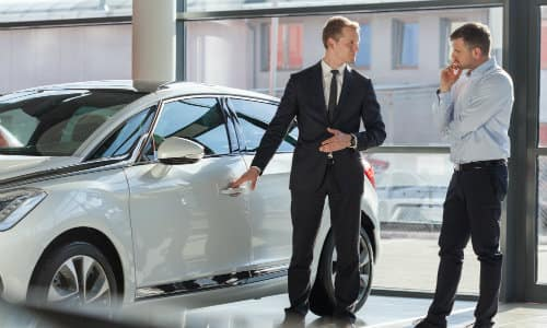 a car dealership sales agent showing a potential customer around