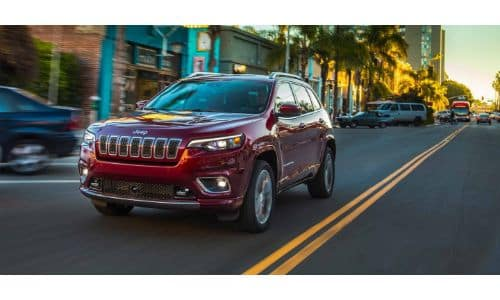 2019 Jeep Cherokee exterior shot with red paint color driving through a suburban downtown city