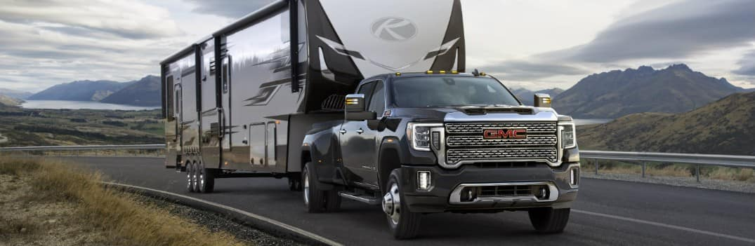 2020 GMC Sierra 3500HD exterior shot towing a massive RV trailer on a country highway