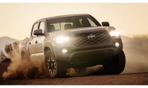 2020 Toyota Tacoma TRD off-road exterior shot with cement paint color driving on a dirt road as dust clouds kick up in the wheels