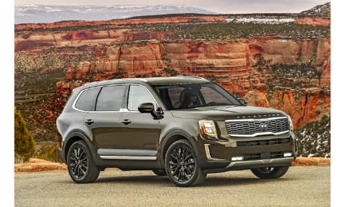 2020 Kia Telluride exterior shot with dark moss green paint color parked on gravel near orange cliffs