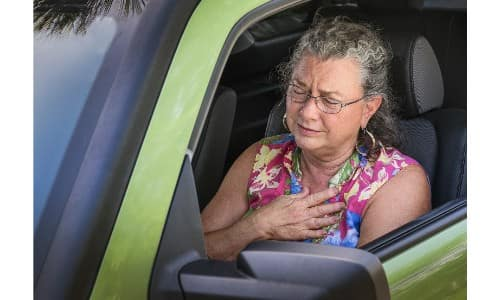 older senior woman driving car hot, overheated, and frustrated while feeling sick