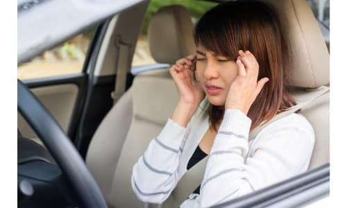 young woman driving car with a headache and rubbing her temples to relieve stress