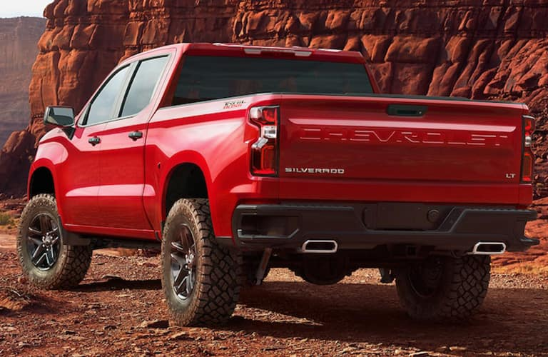 2019 Chevy Silverado exterior rear shot with red paint color and model name imprint on truck bed bumper with a red rock mountain background