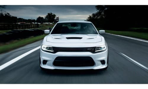 2019 Dodge Charger exterior front shot of grille, headlights, and fascia with white paint color driving down a country highway