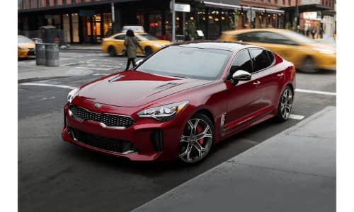 2019 Kia Stinger exterior shot with red paint color parked in a busy city as traffic and cabs rush by