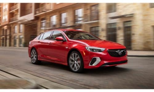 2020 Buick Regal GS exterior shot with red paint color driving through a city