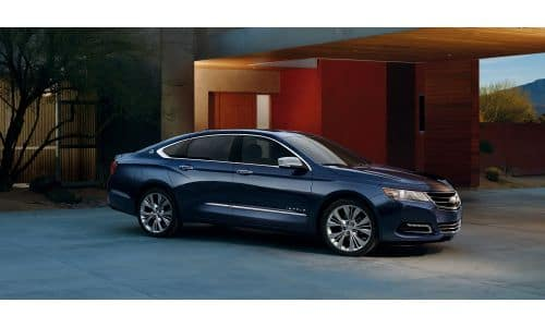 2020 Chevy Impala exterior side shot with dark blue paint color parked outside a luxury home in the evening