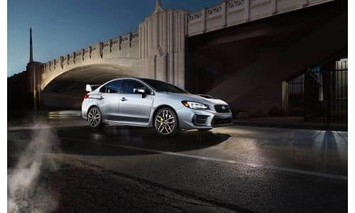 2020 Subaru WRX STI exterior side shot with gray metallic paint color parked by a bridge at night
