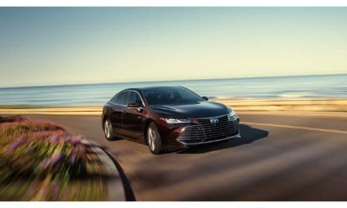 2020 Toyota Avalon exterior shot with red purple paint color driving on a highway near a beach